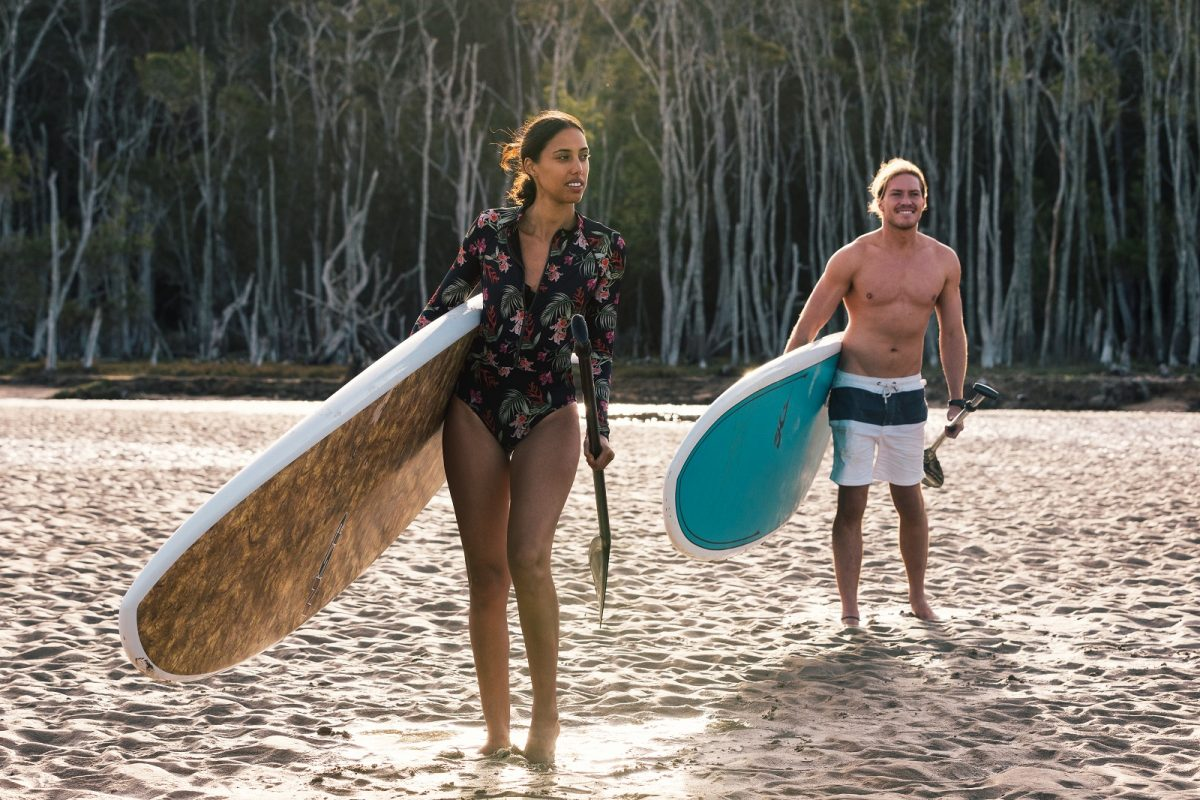 A woman and a man with paddle boards on the sand in Durras lake