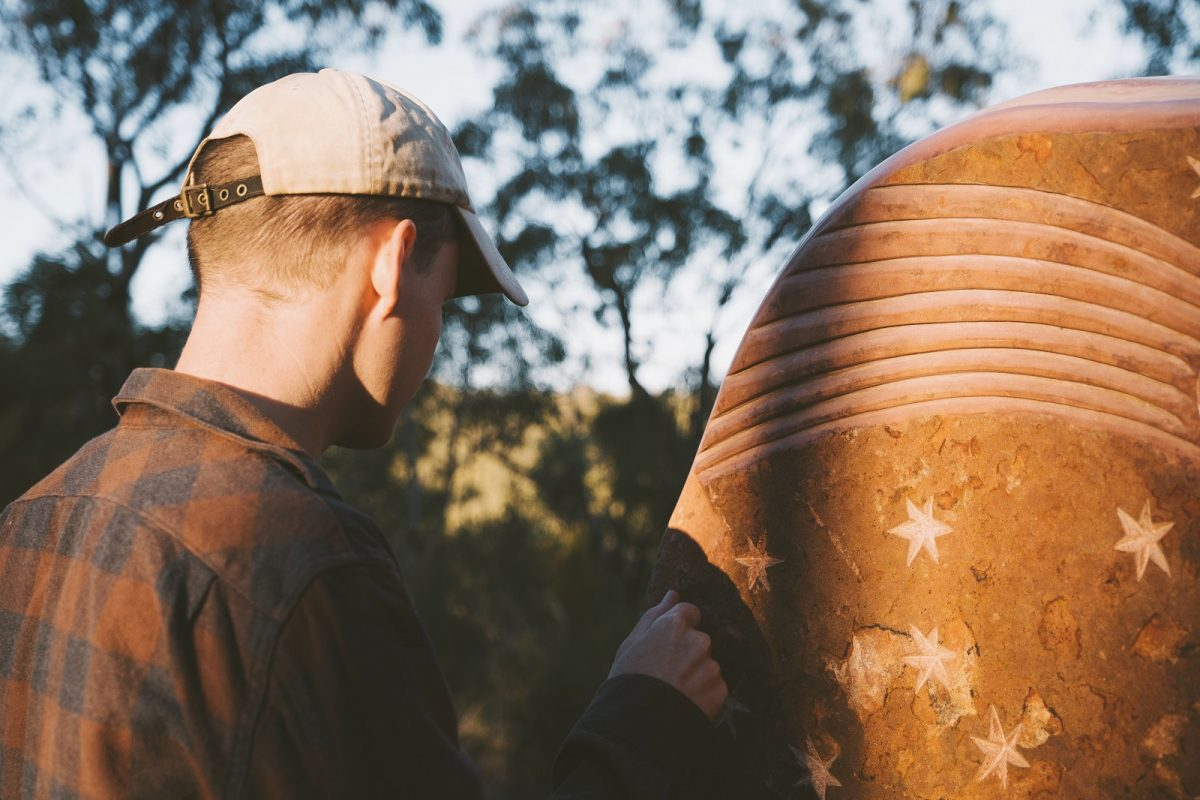 A man with a close up look of a sculpture in the Sculptures in the Scrub walking track. Photo: Harrison Candlin/OEH