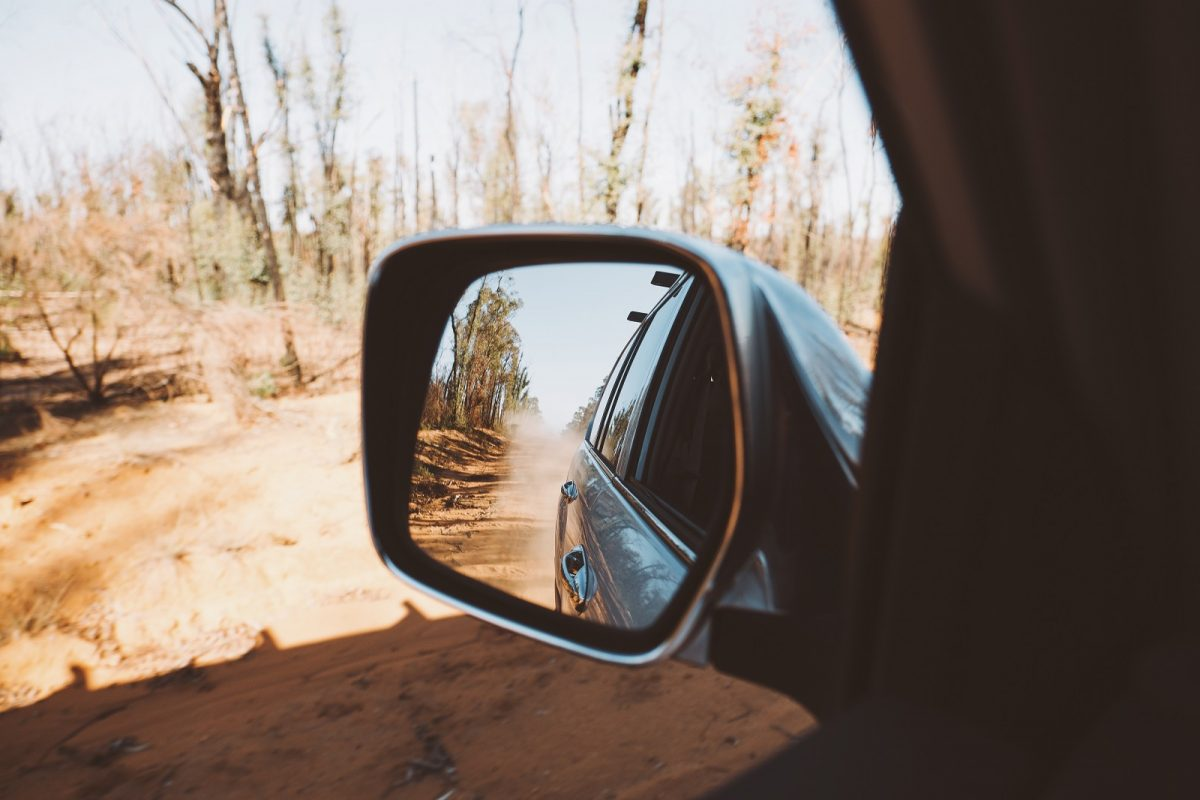 Wing mirror view of the road in Timmallallie National Park. Photo: Harrison Candlin/OEH