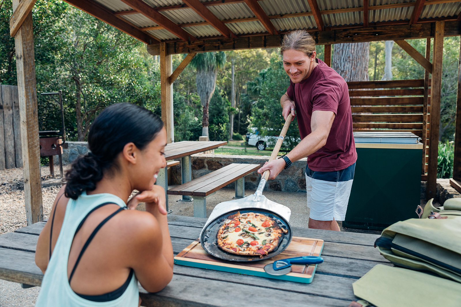 A male and a female enjoying woodfired pizza in Murramarang National Park