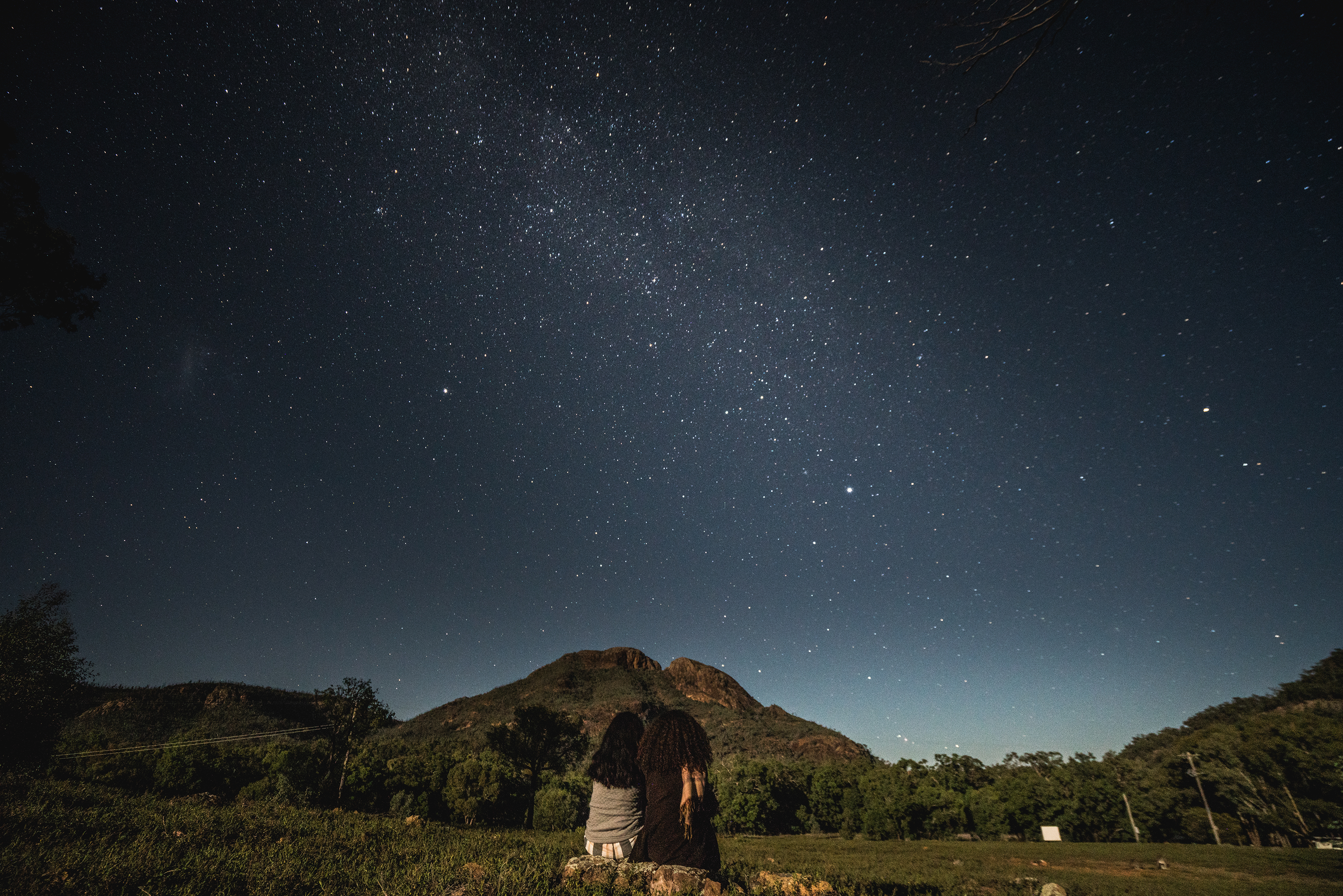 Two females sitting looking at the night sky in Warrumbungles National Park