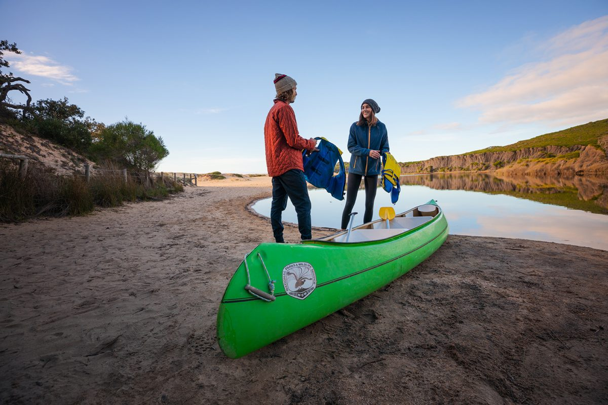 A couple putting on their life jackets to go canoeing in the lagoon in Bournda national park