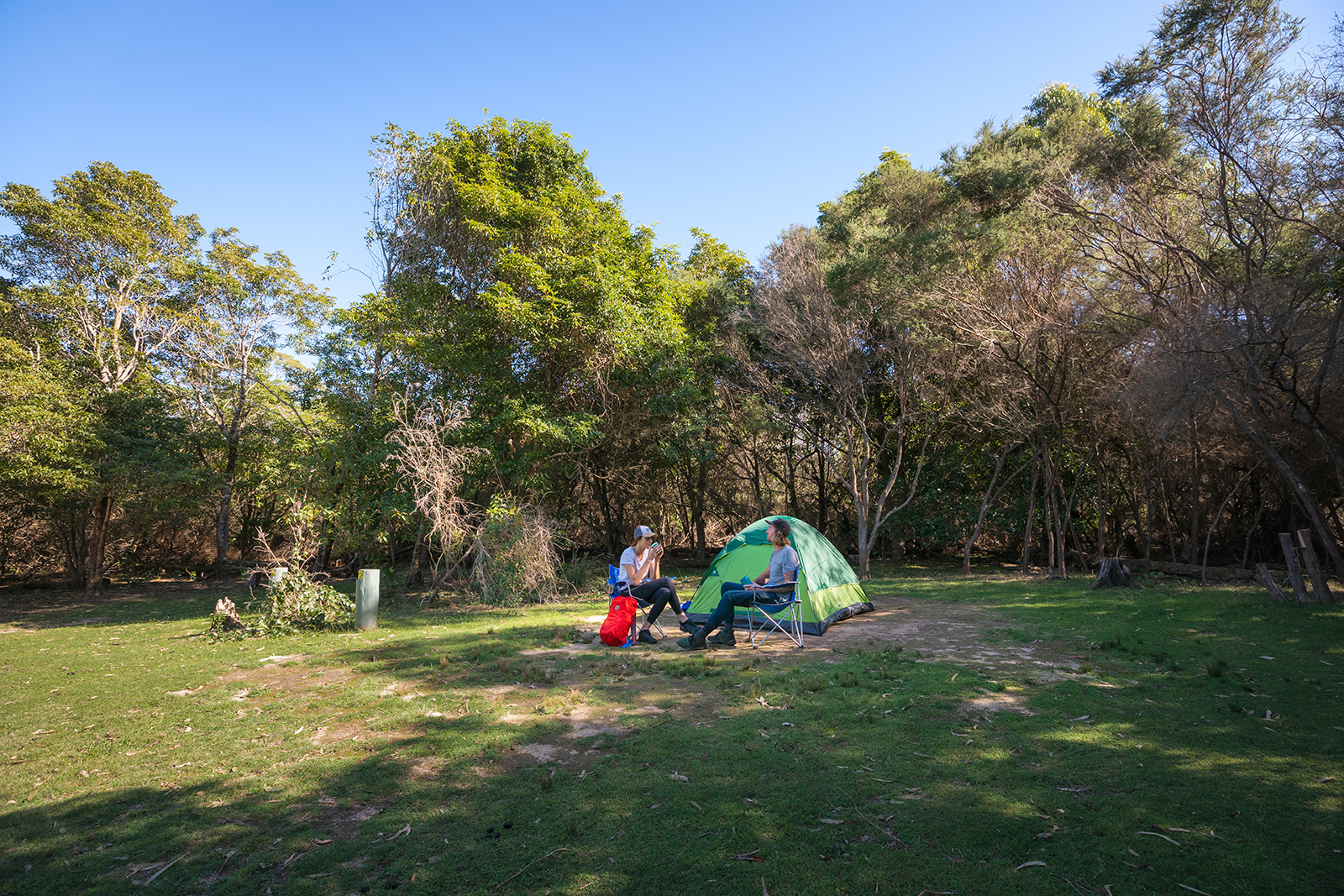 A couple sitting in camp chairs in front of their tent in Hobart beach campground, Bournda National Park