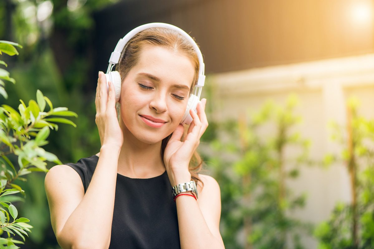A woman with her eyes closed and earphones on enjoying what she is listening to