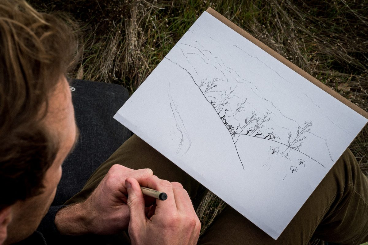 A male with a pen in his hand sketching