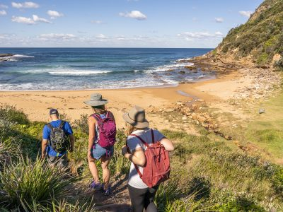 Three people hiking on the Bouddi Coastal walk near Little Beach campground, Bouddi National Park