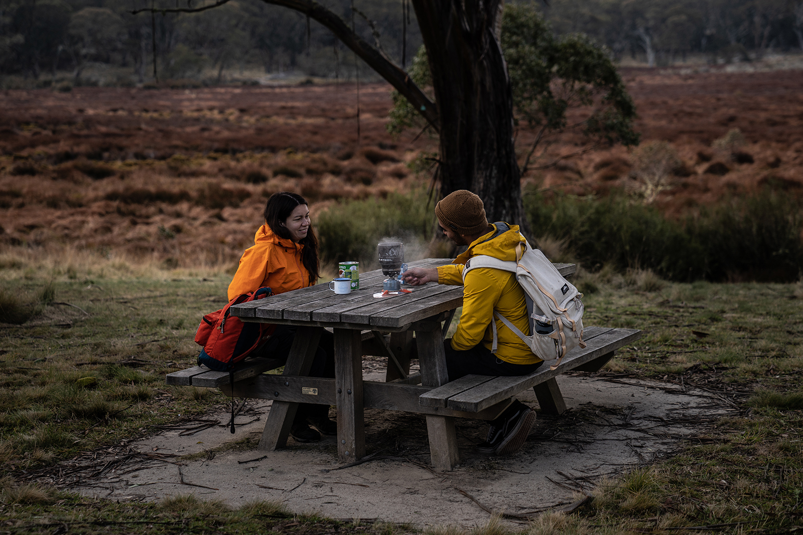 Two people enjoying a hot drink on a picnic bench