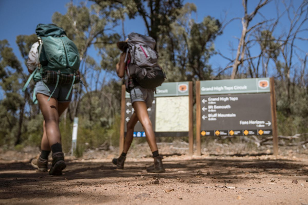 Two people walking past a sign in Warrumbungles National Park