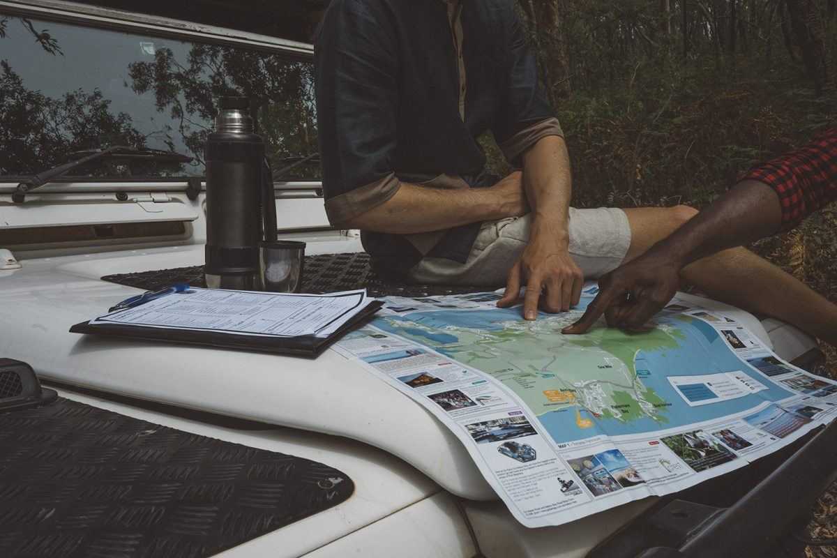 Two people looking at a a map on the hood of their car