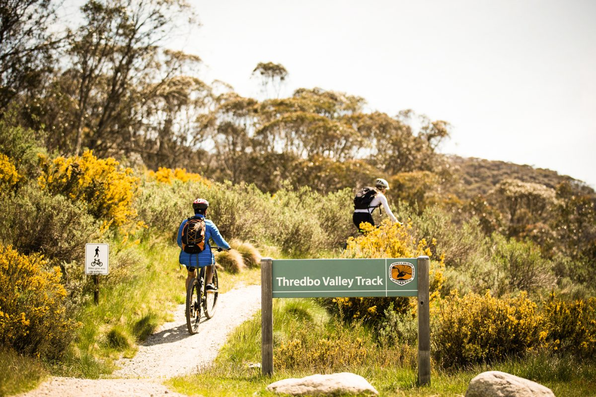 Two people passing the start of the Thredbo Valley Track
