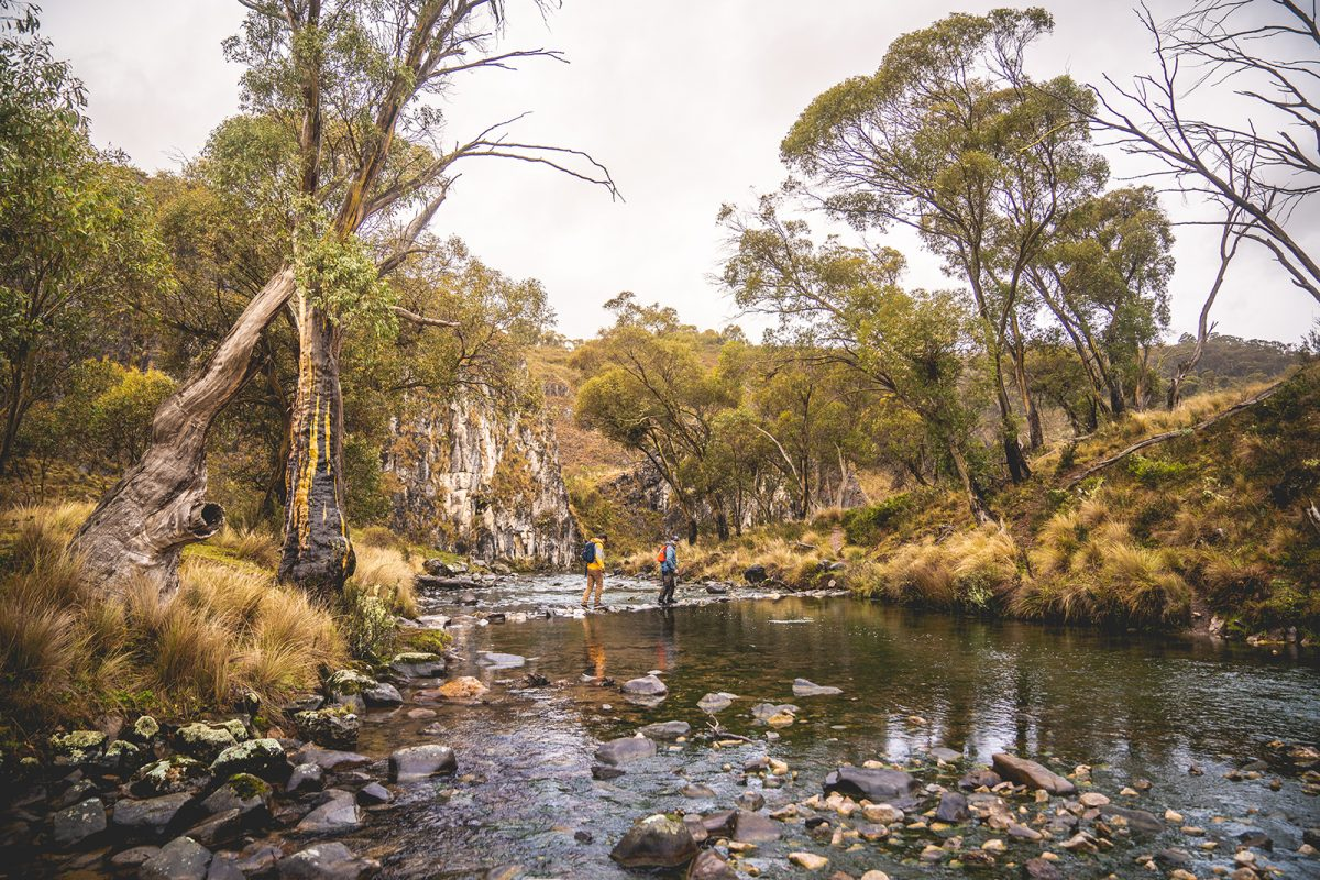 Two people crossing Clarke Gorge , kosciuszko National Park