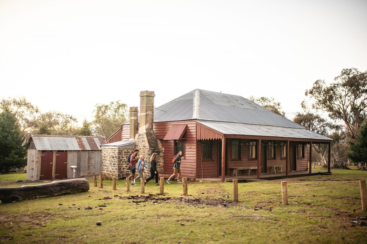 Four people walking past The Pines cottage in Kosciuszko National Park