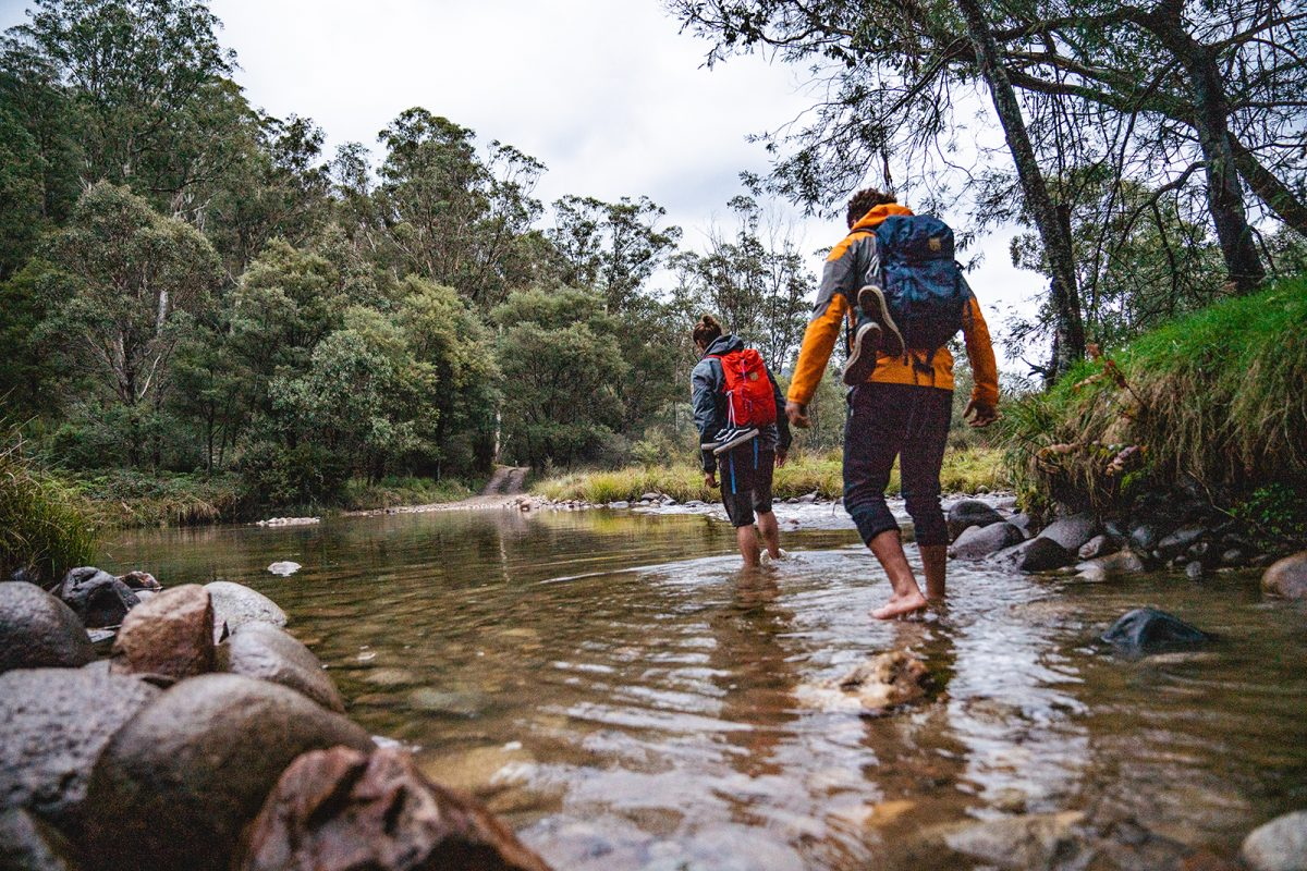 Two people crossing the Swampy Plains River in Kosciuszko National Park. Photo: Rob Mulally/DPIE