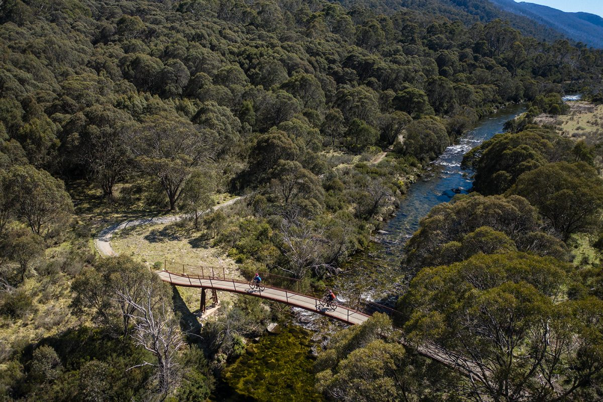 Aerial view of two people riding across a suspension bridge on the Thredbo Valley Track