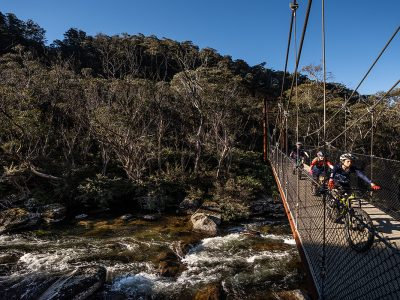 Group riding across bridge on the Thredbo Valley track, Thredbo-Perisher area in Kosciuszko National Park