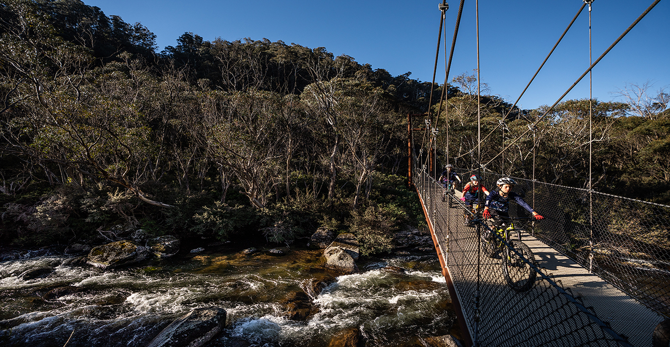 Group riding across bridge on the Thredbo Valley track, Thredbo-Perisher area in Kosciuszko National Park. Photo: Rob Mulally/DPIE