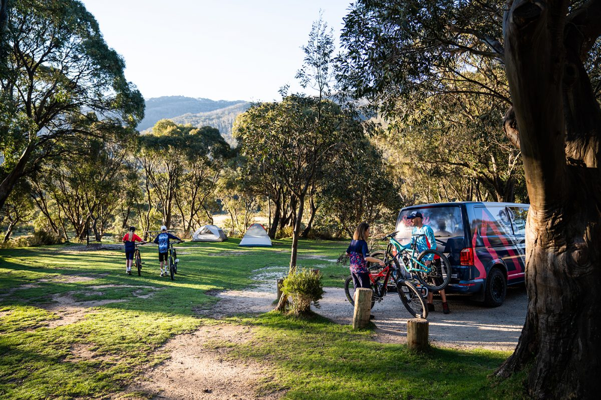 Four people walking their bikes to their tents in Thredbo Diggings campground
