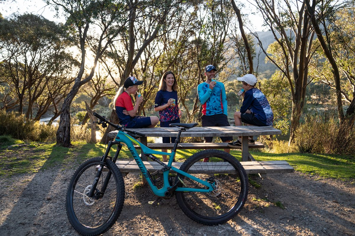 Family of four enjoying poppers at a picnic table in Thredbo Diggings campground