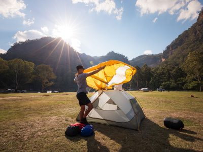 Person setting up a tent at Newnes campground, Wollemi National Park. Photo: Daniel Tran/DPIE