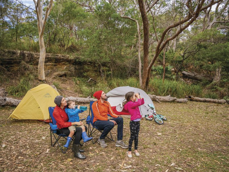 A family with two parents and two young kids Birdwatching, Bonnie Vale Campground, Royal National Park. Photo: John Spencer / DPIE