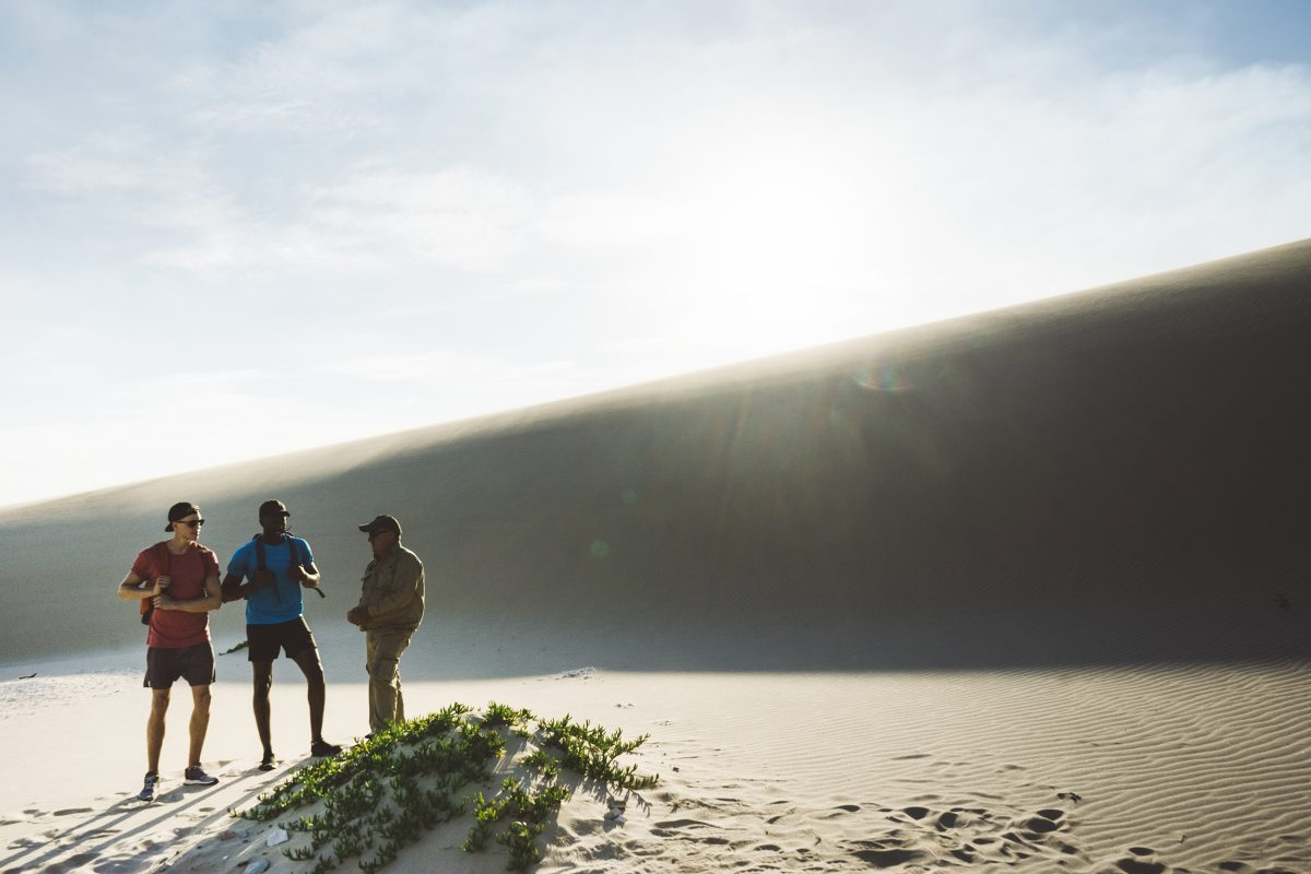A tour guide talks to two people in Worimi State Conservation Lands. Photo: Erin Mc Gawley